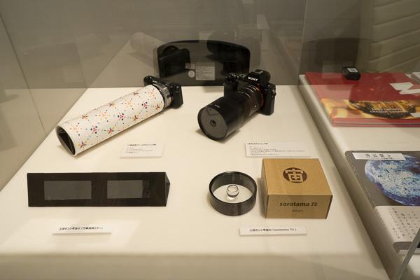 撮影機材の展示コーナー。宙玉や万華鏡のミラーは階下の「NADiff du Champ」 にて購入可能です。本や缶バッチなどもあります。